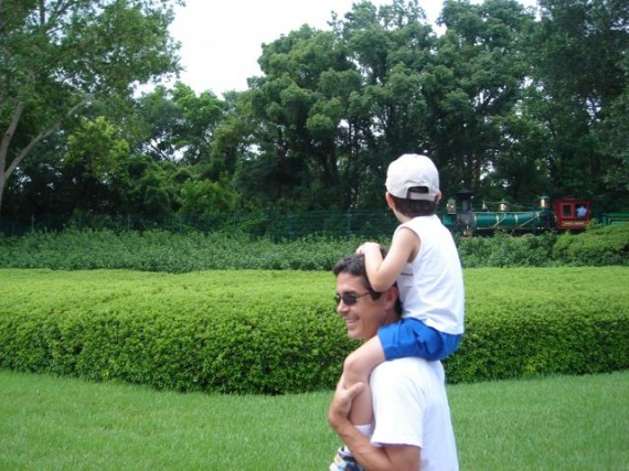 Dad carrying son on shoulders watching Walt Disney World Railroad train