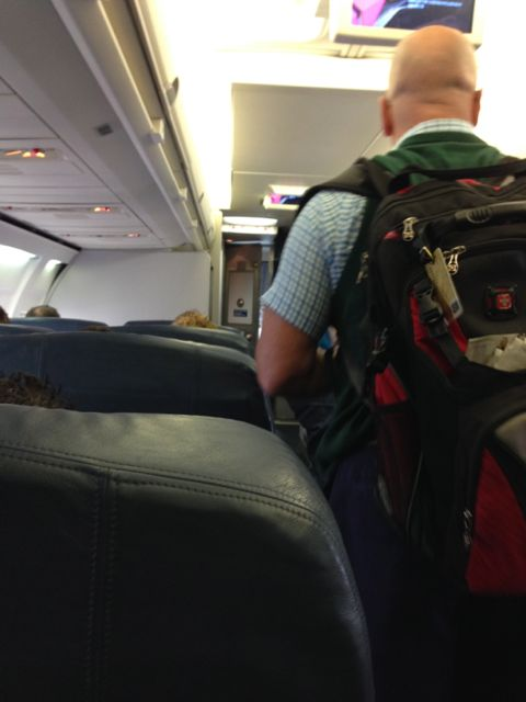 Businessman with backpack in Delta first class cabin