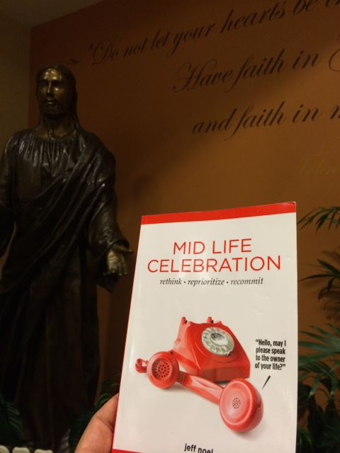 Mid Life Celebration book with Jesus statue in background
