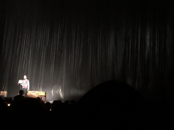 One man on giant dark stage, with spotlight
