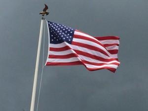 American Flag blowing in the wind with dark skies behind it