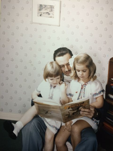 Walt Disney with his daughters sitting on his lap