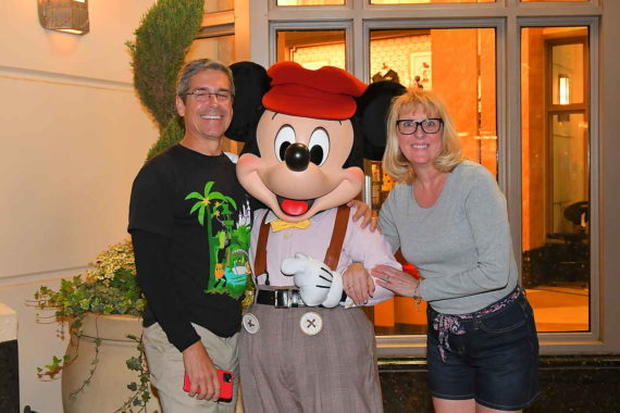 Married couple posing with Mickey Mouse