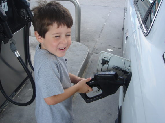 small child pumping gas