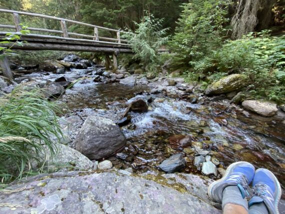 bridge over creek with hikers shoes in foreground