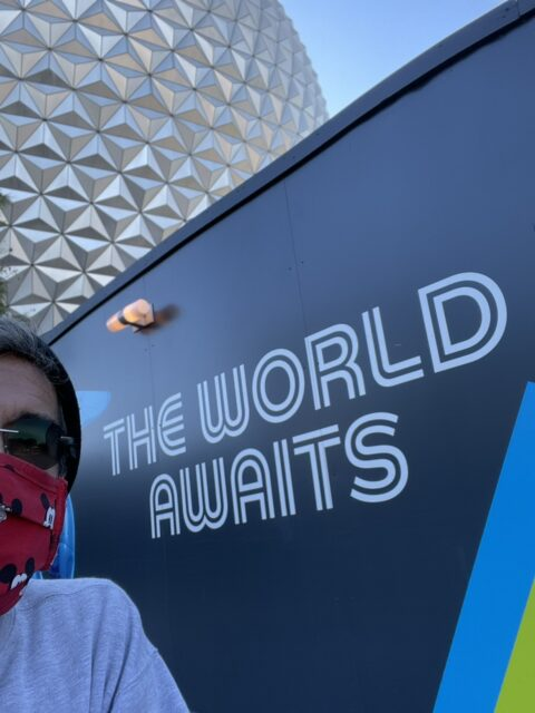 Man by a sign with spaceship Earth behind him