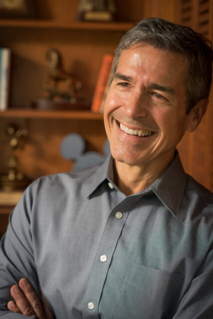 Man smiling in front of bookshelf
