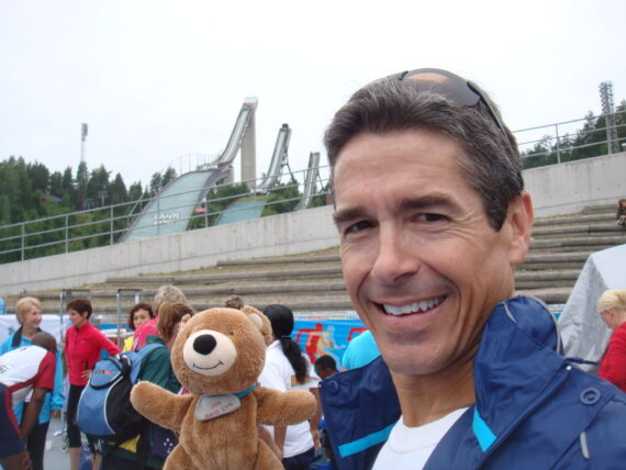 Man holding teddy bear with ski jumps in the background