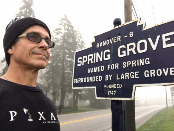 Man standing next to a sign for the small town Spring Grove, Pennsylvania