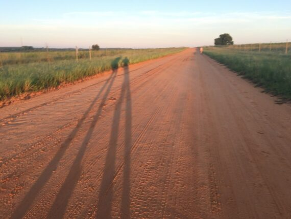Too long shadows of humans on a dirt road