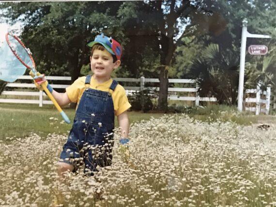 child with butterfly net in flower meadow