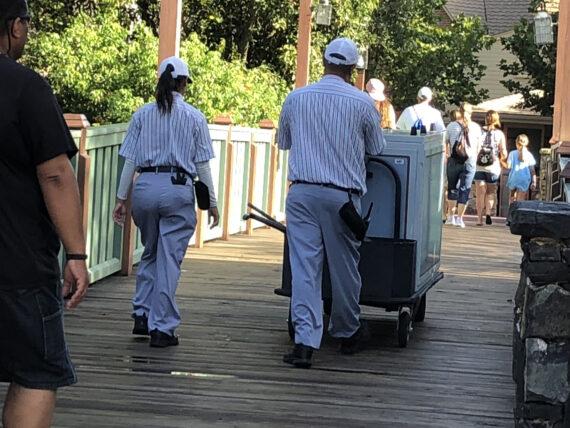 two custodial Cast members crossing a bridge