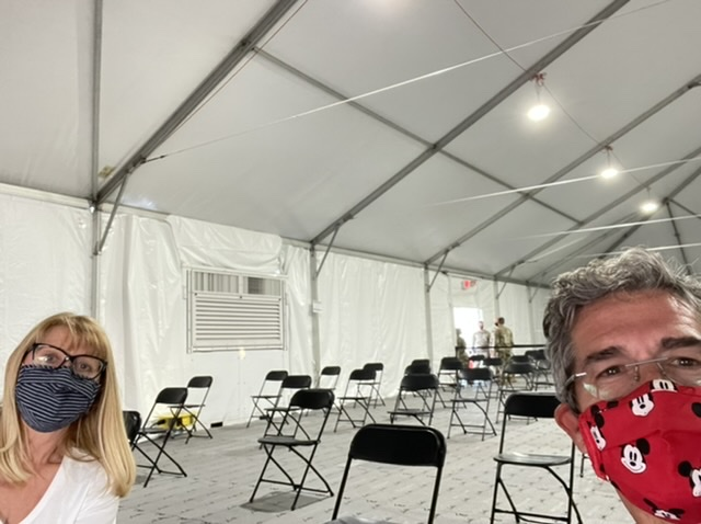 masked couple in large empty tent